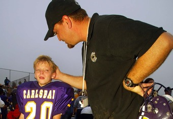 CARLSBAD, CA - NOVEMBER 9:  A coach of the Carlsbad Mighty Lancers (8&under) consoles one of his players after his team's loss to the Torrey Pines Falcons during the Pop Warner Division Finals on November 9, 2002 at Carlsbad High School, in Carlsbad, Cali