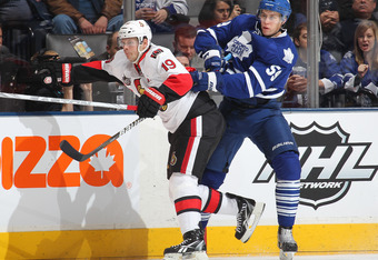 TORONTO, CANADA - JANUARY 17:  Keith Aulie #59 of the Toronto Maple Leafs slams into Jason Spezza #19 of the Ottawa Senators on January 17, 2012 at the Air Canada Centre in Toronto, Ontario, Canada. The Senators defeated the Leafs 3-2. (Photo by Claus And