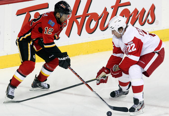 CALGARY, CANADA - JANUARY 31: Jarome Iginla #12 of the Calgary Flames jockeys for the puck with Mike Commodore #22 of the Detroit Red Wings in third period NHL action on January 31, 2012 at the Scotiabank Saddledome in Calgary, Alberta, Canada. (Photo by