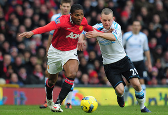 MANCHESTER, ENGLAND - FEBRUARY 11: Antonio Valencia of Manchester United is challenged by Jay Spearing of Liverpool during the Barclays Premier League match between Manchester United and Liverpool at Old Trafford on February 11, 2012 in Manchester, Englan