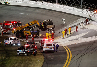 DAYTONA BEACH, FL - FEBRUARY 27:  Safety workers clean up the track after a jet dryer burst into flames after being hit under caution by Juan Pablo Montoya, driver of the #42 Target Chevrolet, during the NASCAR Sprint Cup Series Daytona 500 at Daytona Int