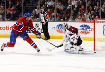 MONTREAL, CANADA - OCTOBER 15:  Travis Moen #32 of the Montreal Canadiens scores a second-period goal on Semyon Varlamov #1 of the Colorado Avalanche during the NHL game at the Bell Centre on October 16, 2011 in Montreal, Quebec, Canada.  (Photo by Richar