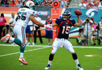 MIAMI GARDENS, FL - OCTOBER 23: Tim Tebow #15 of the Denver Broncos passes despite pressure by Koa Misi #55 of the Miami Dolphins at Sun Life Stadium on October 23, 2011 in Miami Gardens, Florida. (Photo by Scott Cunningham/Getty Images)