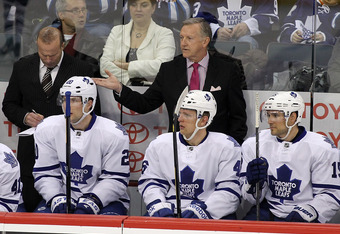 WINNIPEG, CANADA - FEBRUARY 7: Head coach Ron Wilson of the Toronto Maple Leafs questions one of his players from the bench as players David Steckel #20, Joey Crabb #46 and Matthew Lombardi #15 look on during a game against the Winnipeg Jets in NHL action