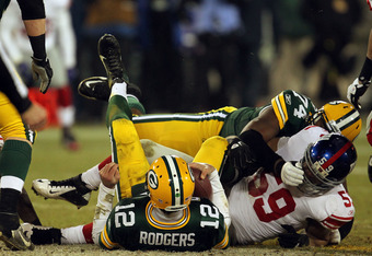 GREEN BAY, WI - JANUARY 15:  Aaron Rodgers #12 of the Green Bay Packers gets sacked by Michael Boley #59 of the New York Giants in the fourth quarter of their NFC Divisional playoff game at Lambeau Field on January 15, 2012 in Green Bay, Wisconsin.  (Phot