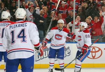 BUFFALO, NY - FEBRUARY 17:  Scott Gomez #11 of the Montreal Canadiens celebrates a first period power play goal against the Buffalo Sabres with teammates Yannick Weber #68, Tomas Plekanec #14, and Andrei Kostitsyn #46 during their NHL game at First Niagar