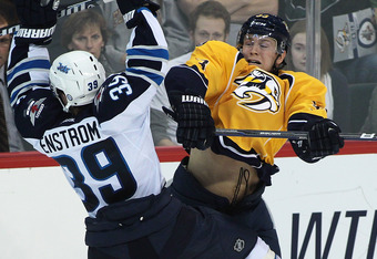 WINNIPEG, CANADA - SEPTEMBER 30: Tobias Enstrom #39 of the Winnipeg Jets collides with Colin Wilson #33 of the Nashville Predators in preseason NHL action at the MTS Centre on September 30, 2011 in Winnipeg, Manitoba, Canada. (Photo by Marianne Helm/Getty