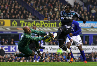 LIVERPOOL, ENGLAND - FEBRUARY 11:  Tim Howard of Everton dives to block the attempt on goal of  Romelu Lukaku of Chelsea during the Barclays Premier League match between Everton and Chelsea at Goodison Park on February 11, 2012 in Liverpool, England.  (Ph