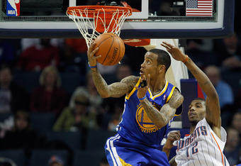 CHARLOTTE, NC - JANUARY 14:  Monta Ellis #8 of the Golden State Warriors shoots the ball over Tyrus Thomas #12 of the Charlotte Bobcats during their game at Time Warner Cable Arena on January 14, 2012 in Charlotte, North Carolina.  NOTE TO USER: User expr