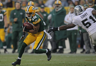 GREEN BAY, WI - DECEMBER 11:  Randall Cobb #18 of the Green Bay Packers moves past Aaron Curry #51 of the Oakland Raiders at Lambeau Field on December 11, 2011 in Green Bay, Wisconsin. The Packers defeated the Raiders 46-16.  (Photo by Jonathan Daniel/Get