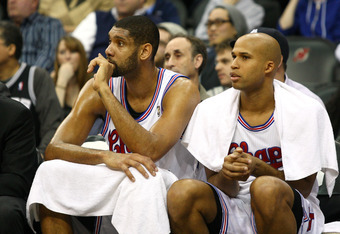 NEWARK, NJ - FEBRUARY 11:  (L-R) Tim Duncan #21 and Richard Jefferson #24 of the San Antonio Spurs look on from the bench against the New Jersey Nets at Prudential Center on February 11, 2012 in Newark, New Jersey.  NOTE TO USER: User expressly acknowledg