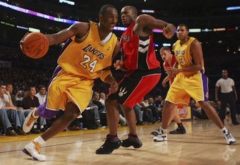 LOS ANGELES, CA - NOVEMBER 17: Kobe Bryant #24 of the Los Angeles Lakers drives to the basket past Fred Jones #20 of the Toronto Raptors during the second half of the game on November 17, 2006 at Staples Center in Los Angeles, California. The Lakers defea