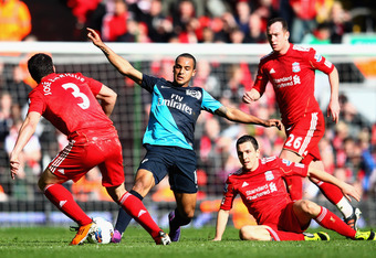 LIVERPOOL, ENGLAND - MARCH 03:  Theo Walcott of Arsenal battles for the ball against Jose Enrique and  Stewart Downing of Liverpool during the Barclays Premier League match between Liverpool and Arsenal at Anfield on March 3, 2012 in Liverpool, England.