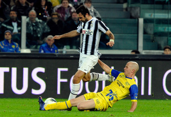 TURIN, ITALY - MARCH 03:  Mirko Vucinic of Juventus FC and Michael Bradley of AC Chievo Verona compete for the ball during the Serie A match between Juventus FC and AC Chievo Verona at Juventus Arena on March 3, 2012 in Turin, Italy.  (Photo by Claudio Vi
