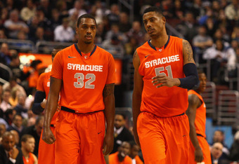 PHILADELPHIA, PA - JANUARY 11:  (L-R) Kris Joseph #32 and Fab Melo #51 of the Syracuse Orange talk as they walk on the court against the Villanova Wildcats at the Wells Fargo Center on January 11, 2012 in Philadelphia, Pennsylvania.  (Photo by Chris Chamb