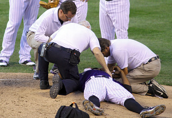 DENVER, CO - AUGUST 5: Pitcher Juan Nicasio #44 of the Colorado Rockies is attended to by medical staff on the mound after being hit in the face by a ball while pitching against the Washington Nationals during their game at Coors Field August 5, 2011 in D