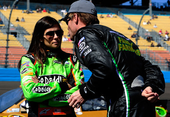 AVONDALE, AZ - MARCH 03:  (L-R) Danica Patrick, driver of the #7 GoDaddy.com Chevrolet, talks with Kenny Wallace, driver of the #09 RAB Racing with Brack Maggard Toyota, on the grid during qualifying for the NASCAR Nationwide Series Bashas' Supermarkets 2