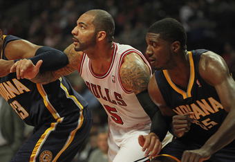 CHICAGO, IL - DECEMBER 20:  Carlos Boozer #5 of the Chicago Bulls sets for a rebound between Danny Granger #33 and Roy Hibbert #55 of the Indiana Pacers at the United Center on December 20, 2011 in Chicago, Illinois. The Bulls defeated the Pacers 93-85. N