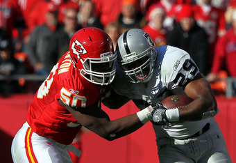 KANSAS CITY, MO - DECEMBER 24:  Justin Houston #50 of the Kansas City Chiefs tackles Michael Bush #29 of the Oakland Raiders as Bush carries the ball upfield during the game on December 24, 2011 at Arrowhead Stadium in Kansas City, Missouri.  (Photo by Ja