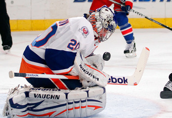 NEW YORK, NY - DECEMBER 26: Goalie Evgeni Nabokov #20 of the New York Islanders makes a save in an NHL hockey game against the New York Rangers at Madison Square Garden on December 26, 2011 in New York City.  (Photo by Paul Bereswill/Getty Images)