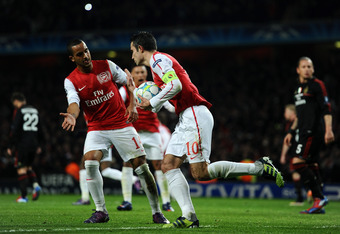 LONDON, ENGLAND - MARCH 06:  Theo Walcott congratulates Robin van Persie of Arsenal after he scored their third goal from the penalty spot during the UEFA Champions League Round of 16 second leg match between Arsenal and AC Milan at Emirates Stadium on Ma