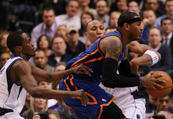 DALLAS, TX - MARCH 06:  Carmelo Anthony #7 of the New York Knicks dribbles the ball against Shawn Marion #0 and Rodrigue Beaubois #3 of the Dallas Mavericks at American Airlines Center on March 6, 2012 in Dallas, Texas.  NOTE TO USER: User expressly ackno