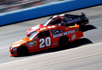 AVONDALE, AZ - MARCH 04:  Joey Logano, driver of the #20 The Home Depot Toyota, drives alongside Tony Stewart, driver of the #14 Office Depot/ Mobil 1 Chevrolet, during the NASCAR Sprint Cup Series SUBWAY Fresh Fit 500 at Phoenix International Raceway on