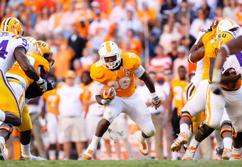 KNOXVILLE, TN - OCTOBER 15:  Tauren Poole #28 of the Tennessee Volunteers rushes through a hole in the line against the LSU Tigers at Neyland Stadium on October 15, 2011 in Knoxville, Tennessee.  (Photo by Kevin C. Cox/Getty Images)