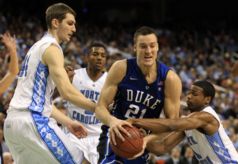 GREENSBORO, NC - MARCH 13:  Miles Plumlee #21 of the Duke Blue Devils moves the ball against Dexter Strickland #1 and Tyler Zeller #44 of the North Carolina Tar Heels during the first half in the championship game of the 2011 ACC men's basketball tourname