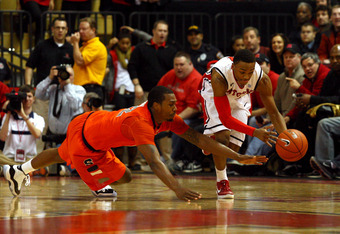 NEW BRUNSWICK, NJ - FEBRUARY 19:  Myles Mack #4 of the Rutgers Scarlet Knights attempts to control a loose ball against Kris Joseph #32 of the Syracuse Orange in the second half at Louis Brown Athletic Center on February 19, 2012 in New Brunswick, New Jer