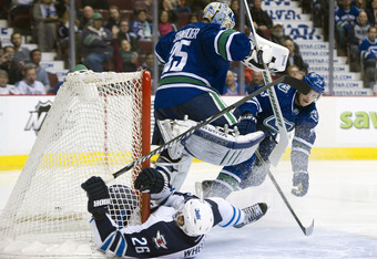 VANCOUVER, CANADA - MARCH 8: Blake Wheeler #26 of the Winnipeg Jets crashes into the goal post after slinding past goalie Cory Schneider #35 of the Vancouver Canucks after getting tripped by Alexander Edler #23 of the Vancouver Canucks during the second p