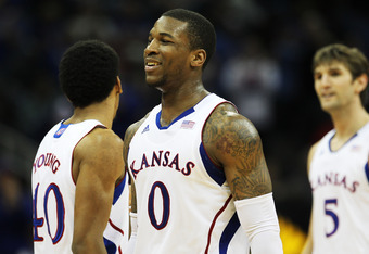 KANSAS CITY, MO - MARCH 08:  Thomas Robinson #0, Kevin Young #40 and Jeff Withey #5 of the Kansas Jayhawks react in the second half against the Texas A&M Aggies during the quarterfinals of the 2012 Big 12 Men's Basketball Tournament at Sprint Center on Ma