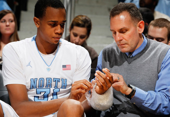 ATLANTA, GA - MARCH 09:  John Henson #31 of the North Carolina Tar Heels receives assistance from Head Athletic Trainer Chris Hirth after being injured in their game against the Maryland Terrapins during the Quarterfinals of the 2012 ACC Men's Basketball