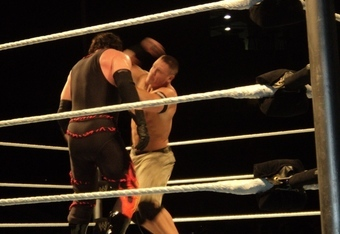 John Cena hits Kane with the microphone.