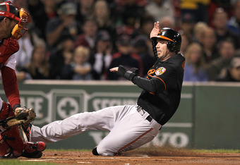 BOSTON, MA - SEPTEMBER 19:  J.J. Hardy #2 of the Baltimore Orioles scores a run in the first inning in the second game of a doubleheader against the Boston Red Sox at Fenway Park September 19, 2011 in Boston, Massachusetts. (Photo by Jim Rogash/Getty Imag