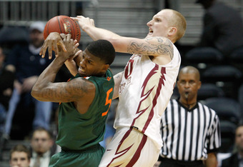 ATLANTA, GA - MARCH 09:  DeQuan Jones #5 of the Miami Hurricanes attempts to control against Jon Kreft #50 of the Florida State Seminoles in their Quarterfinal game of the 2012 ACC Men's Basketball Conferene Tournament at Philips Arena on March 9, 2012 in