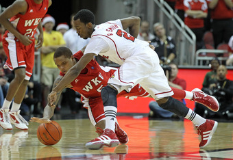 LOUISVILLE, KY - DECEMBER 23:  Russ Smith #2 of the Louisville Cardinals and Derrick Gordon #5 of the Western Kentucky Hilltoppers reach for a loose ball during the game at KFC YUM! Center on December 23, 2011 in Louisville, Kentucky.  Louisville won 70-6