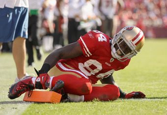 SAN FRANCISCO, CA - OCTOBER 09:  Josh Morgan #84 of the San Francisco 49ers grabs his ankled after being injured in their game against the Tampa Bay Buccaneers at Candlestick Park on October 9, 2011 in San Francisco, California.  (Photo by Ezra Shaw/Getty