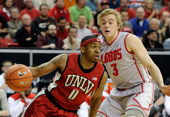LAS VEGAS, NV - MARCH 09:  Oscar Bellfield #0 of the UNLV Rebels drives against Hugh Greenwood #3 of the New Mexico Lobos during a semifinal game of the Conoco Mountain West Conference Basketball tournament at the Thomas & Mack Center March 9, 2012 in Las