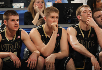 INDIANAPOLIS, IN - MARCH 09: (L-R) Ryne Smith #24, Travis Carroll #50 and Robbie Hummel #24 of the Purdue Boilermakers watch the final minutes from the bench of a loss to the Ohio State Buckeyes during the Big Ten Basketball Tournament Quarterfinals at Ba