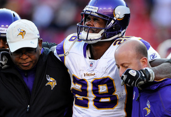 LANDOVER, MD - DECEMBER 24: Running back Adrian Peterson #28 of the Minnesota Vikings is helped off the field after being injured in the third quarter against the Washington Redskins at FedEx Field on December 24, 2011 in Landover, Maryland. (Photo by Pat