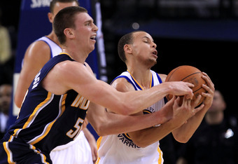 OAKLAND, CA - JANUARY 19:  Stephen Curry #30 of the Golden State Warriors collides with Tyler Hansbrough #50 of the Indiana Pacers at Oracle Arena on January 19, 2011 in Oakland, California.  NOTE TO USER: User expressly acknowledges and agrees that, by d