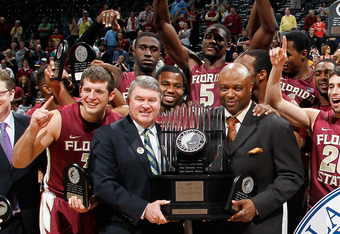 ATLANTA, GA - MARCH 11:  ACC Commissioner John Swofford presents the conference championship trophy to head coach Leonard Hamilton of the Florida State Seminoles and his players after they won 85-82 against the North Carolina Tar Heels during the Final Ga