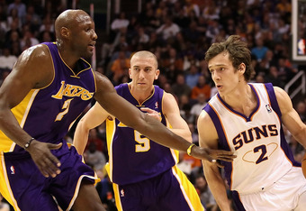 PHOENIX - JANUARY 05: Goran Dragic #2 of the Phoenix Suns drives the ball past Lamar Odom #7 of the Los Angeles Lakers during the NBA game at US Airways Center on January 5, 2011 in Phoenix, Arizona. NOTE TO USER: User expressly acknowledges and agrees th