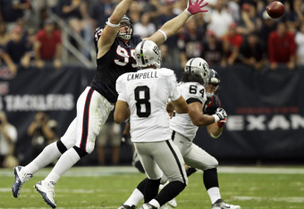 HOUSTON - OCTOBER 09: Defensive end J.J. Watt #99 of the Houston Texans applies pressure as quarterback Jason Campbell #8 of the Oakland Raiders at Reliant Stadium on October 9, 2011 in Houston, Texas. (Photo by Bob Levey/Getty Images)