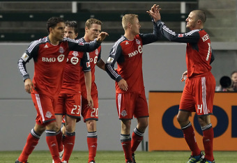CARSON, CA - MARCH 14:  Nick Soolsma (4th from left) #18 of the Toronto FC is congratulated by teammate Danny Koevermans (R) #14 after scoring a goal against the Los Angeles Galaxy in the second half during a CONCACAF Champions League game at The Home Dep