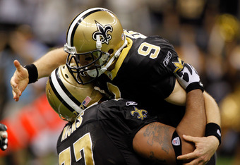 NEW ORLEANS, LA - DECEMBER 26:  Quarterback Drew Brees #9 of the New Orleans Saints is picked up by offensive guard Carl Nicks #77 after Brees throws a nine-yard touchdown pass to running back Darren Sproles #43 and breaks the single-season passing record