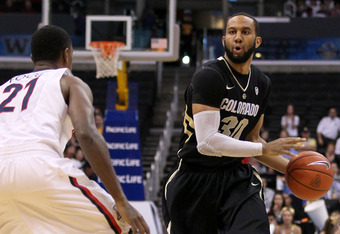 LOS ANGELES, CA - MARCH 10:  Carlon Brown #30 of the Colorado Buffaloes looks to pass the ball as he is covered by Kyle Fogg #21 of the Arizona Wildcats in the first half in the championship game of the Pacific Life Pac-12 basketball tournament at Staples