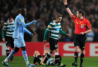 MANCHESTER, ENGLAND - MARCH 15: Referee Tom Harald Hagen shows a yellow card to Yaya Toure of Man City during the UEFA Europa League round of 16 second leg match between Manchester City FC and Sporting Lisbon at Etihad Stadium on March 15, 2012 in Manches
