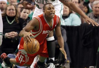 BOSTON, MA - MARCH 06:  Kyle Lowry #7 of the Houston Rockets tries to keep the ball as he trips over Chris Wilcox #44 of the Boston Celtics on March 6, 2012 at TD Garden in Boston, Massachusetts. The Boston Celtics defeated the Houston Rockets 97-92 in ov